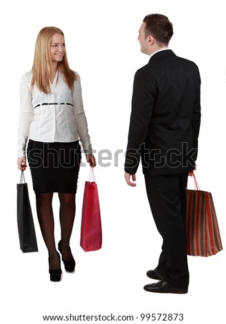 A man and a woman with shopping bags passing by themselves, against a white background.