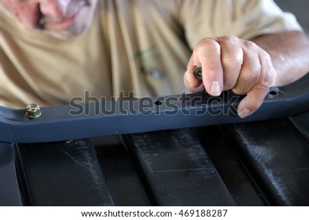 A man assembles lawn furniture by hand