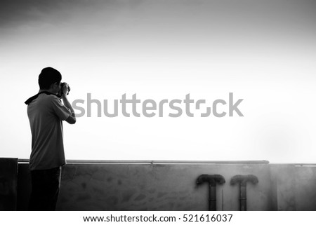 A man enjoying taking photo of fantastic sunrise  at the top of a building with dslr camera