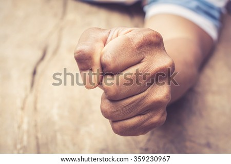 A man fists clenched on a wooden table in anger
