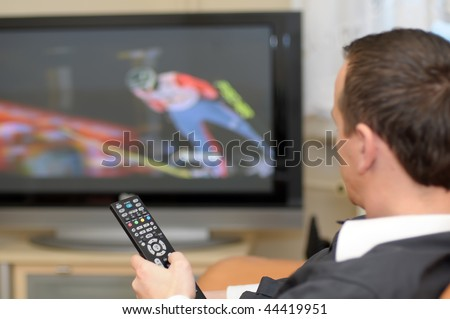 A man holding a remote control while watching a ski jumping on TV.