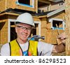 A man in a hard hat standing in front of an house holding a hammer and nail. - stock photo