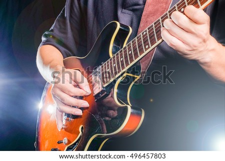 A man is playing the electric guitar on stage. With lighting effect.