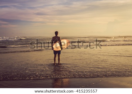 A man is standing with a surf in his hands in the sea shore.