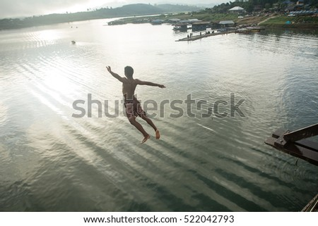 "A man jumping the wooden bridge ""Morn Bridge"" longest wooden bridge in Thailand, Sangkhla Buri District, Kanchanaburi. (Jumping into the water) , (water background)"