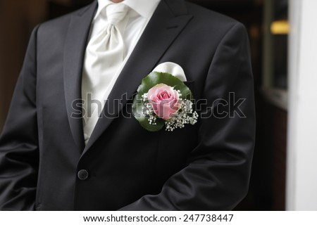 a man on his wedding day in a suit with plugged Rose