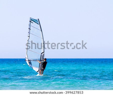 A man on windsurf conquering the waves