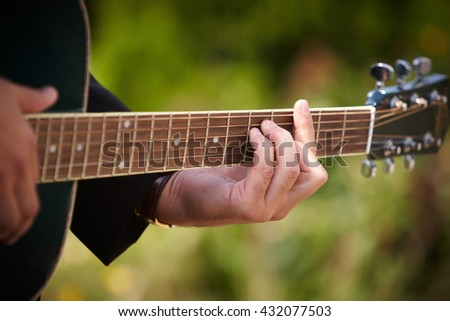A man playing chords on guitar.