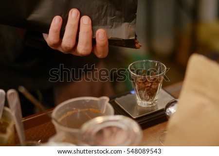A man put coffee beans in a cup for weight