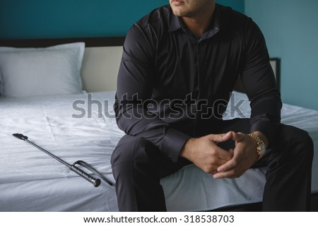 a man sitting on a bed in a black shirt