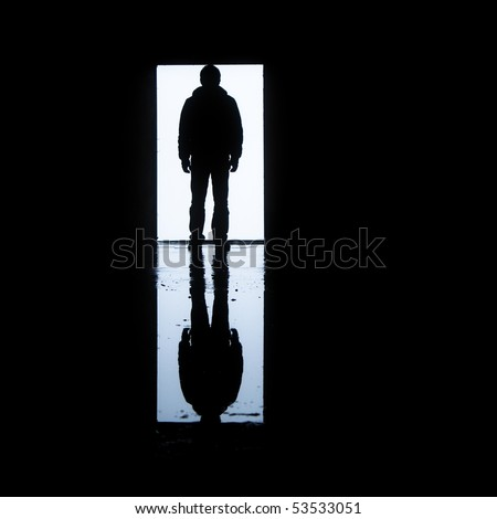 A man standing in front of a door with his image reflected on water