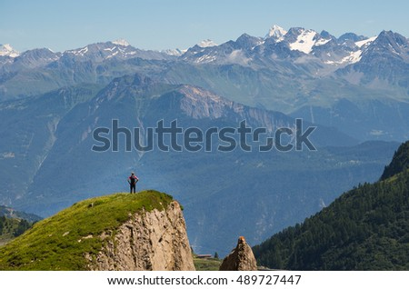 A man standing on a small hill admiring the view of Dent Blanche, a prominent peak in the Swiss alps.