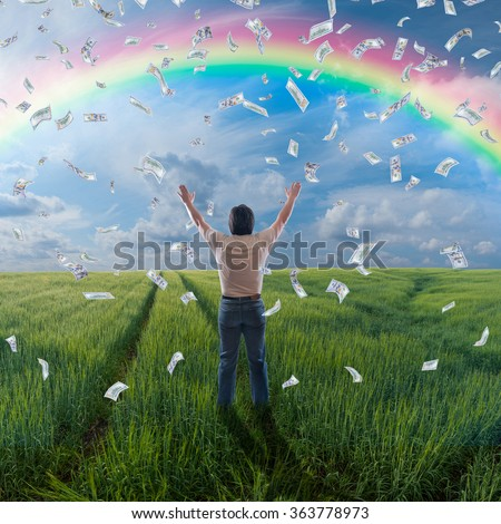 A man standing with open arms under rain from dollars, rainbow in heavens