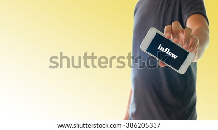 a man using hand holding the smartphone with text inflow on display
