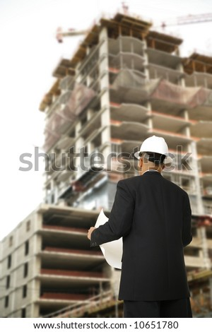 a man wearing hard hat, holding a designer paper and looking at building under construction