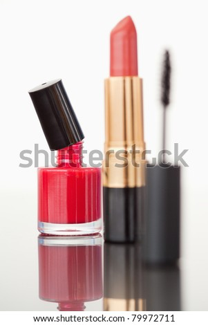 A mascara tube with a pale red lipstick and a red nail polish flask against a white background