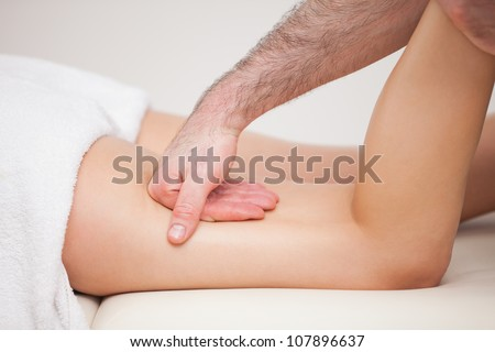 A masseur massaging the thigh of a woman while holding her ankle indoors