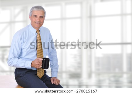 A mature businessman sitting on the corner of his desk in a modern office with a coffee mug in his hand. Horizontal format with copy space.