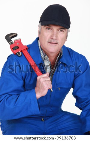 A mature man with a wrench.