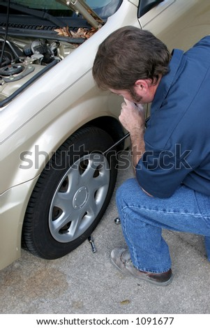 a mechanic removing the hubcap from a car wheel