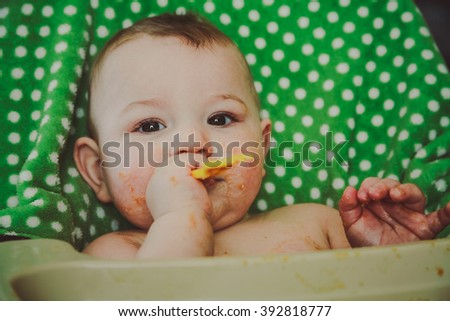 A messy ten month old baby boy sitting in his highchair, chewing on his fork during meal time