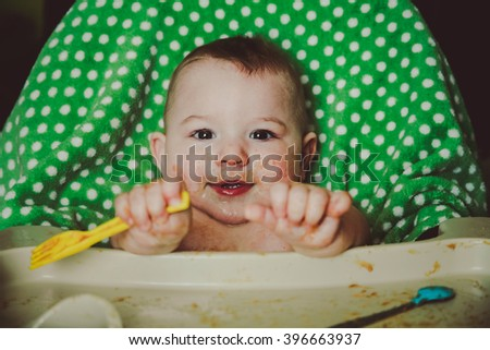 A messy ten month old baby boy sitting in his highchair, playing with his fork during meal time