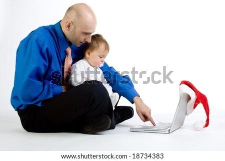 A metaphorical image of a father teaching his baby daughter how to use a computer in a hope to make her a child prodigy.