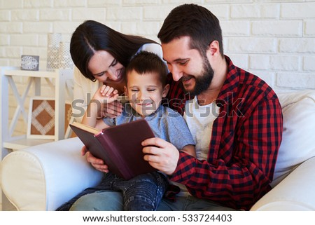 A mid shot of  a nice family sitting on the white armchair, laughing and looking at the book. Mom and dad grinning from ear to ear