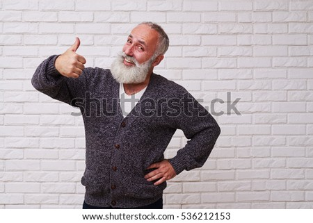 A mid shot of amusing elderly man holding his thumb-up and smiling. Male standing against light background, looking stylish