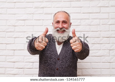 A mid shot of merry smiling widely man, showing his thumbs-up with his two hands. Male wearing grey wooly sweater