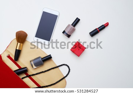 A mid shot of red cosmetics case lying on white field. Accessories of every female including lipstick, pencil, makeup tools
