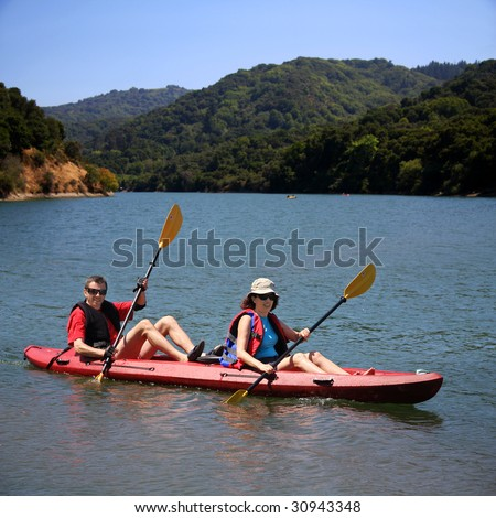 A middle age couple kayaking on the lake