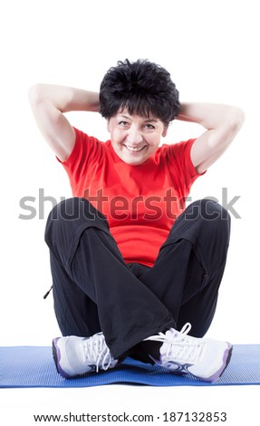 A middle-aged woman in workout clothes doing sit-ups