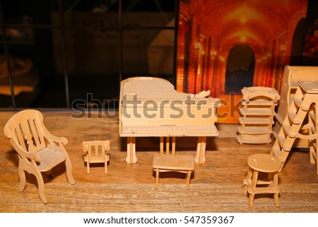 A Miniature of Piano and chairs on the floor / Miniature of Piano and chairs