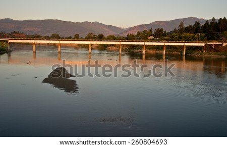 A modern bridge spans the Kootenai River at Bonners Ferry, Idaho.  Early morning light creates a warm glow on the bridge and on the river.
