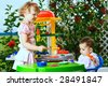 a 6 month old baby and a 4 years old girl in front of toy kitchen - stock photo