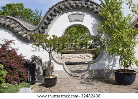 A Moon Gate which is a traditional architectural element in Chinese gardens acts as a pedestrian passageway through a wall
