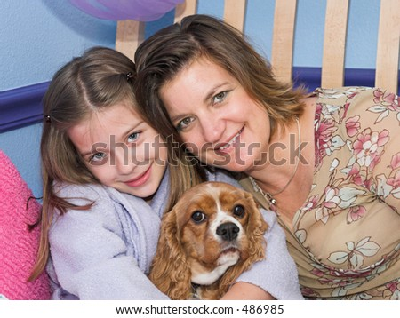 a mother and daughter posing with their cavalier spaniel dog