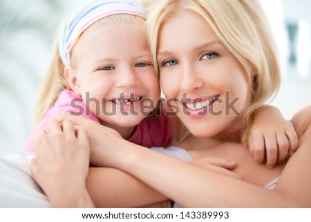 A mother and her daughter hugging and smiling.