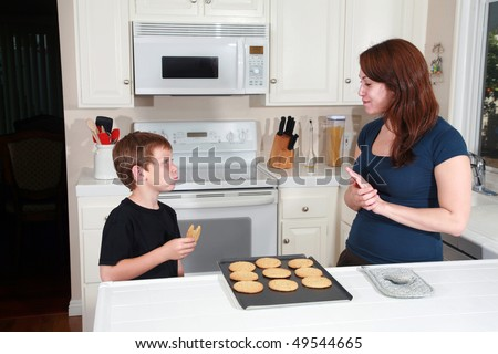 a mother and son enjoy hot fresh baked cookies after school in the kitchen