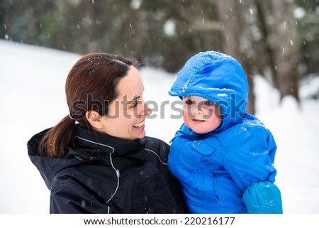 A mother holds her happy baby son smiling at him outside while its snowing during the winter season.  He has a look of wonder on his face.