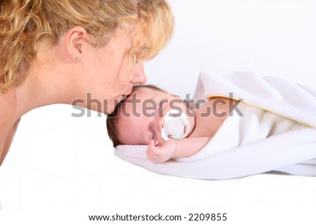 a mother kissing her newborn baby boy