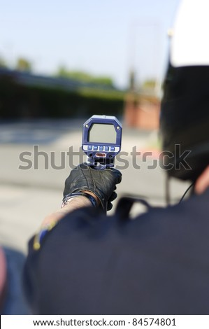 a motorcycle police officer aiming his radar gun a traffic.