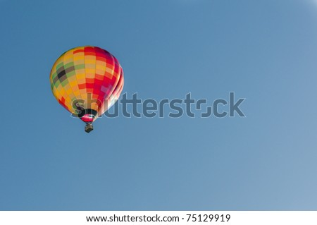 A multicoloured hot air balloon rising in the early morning sunlight into a blue sky.