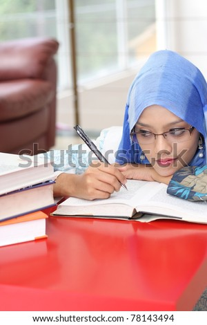 A muslim woman reading a book while looking at the book on the table