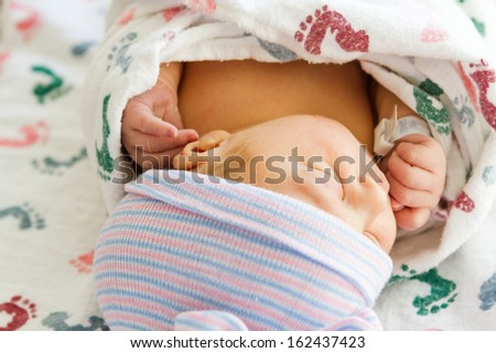 A newborn baby girl wrapped in a swaddle blanket.