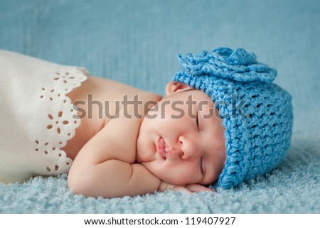 A newborn baby is wearing a blue hat and laying down sleeping on a soft blue background. Soft focuss.