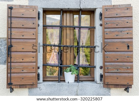 a nice window with open brown  wooden shutters and curtains