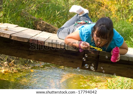 A nine year old girl lying on a wooden bridge blowing bubbles