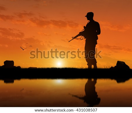 a of a terrorist with a weapon at sunset near the river. The concept of terrorism and war